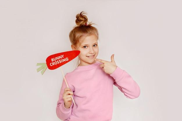 Dziewczyna trzyma marchewkę z napisem zajączek i pokazuje znak ok
