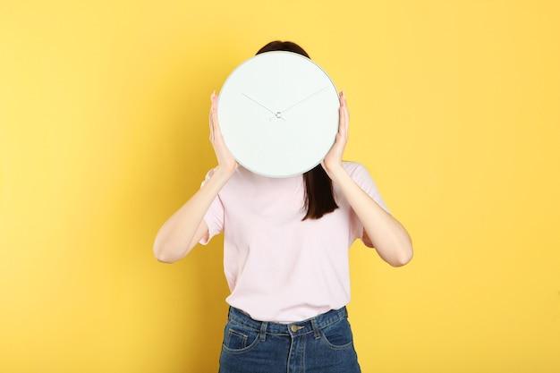Dziewczyna trzyma mechaniczny zegar na kolorowym tle