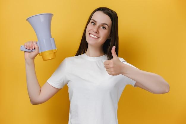 Dziewczyna trzyma megafon i pokazuje kciuk w górę