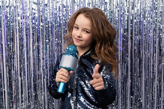 Dziewczyna trzyma mikrofon w jej rękach i pokazuje klasę