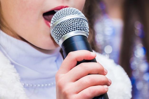 Dziewczyna trzyma mikrofon w ręku podczas wykonywania piosenki na koncercie