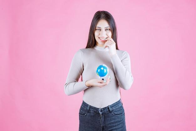 Dziewczyna trzyma mini kulę ziemską i uśmiecha się