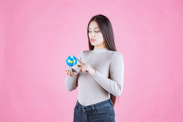 Dziewczyna trzyma mini kulę ziemską i uważnie ją studiuje