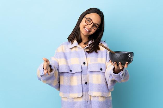 Dziewczyna trzyma miskę pełną makaronów