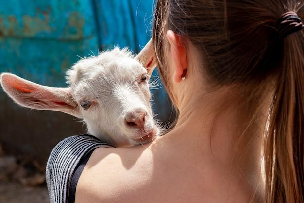 Dziewczyna trzyma młodą kozę. miłość do zwierząt
