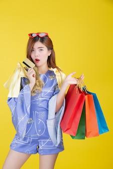 Dziewczyna trzyma modną torbę na zakupy i trzyma kartę inteligentną na żółtym tle.