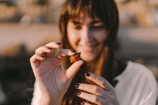 Dziewczyna trzyma na dłoni mieszkańca morza w muszli