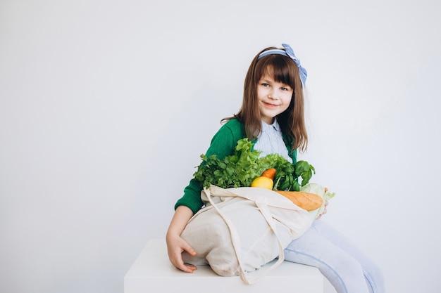 Dziewczyna trzyma na zakupy eko torbę z warzywami, zielenią bez plastiku na tle. zero odpadów, bez plastiku koncepcja przyjazna dla środowiska.