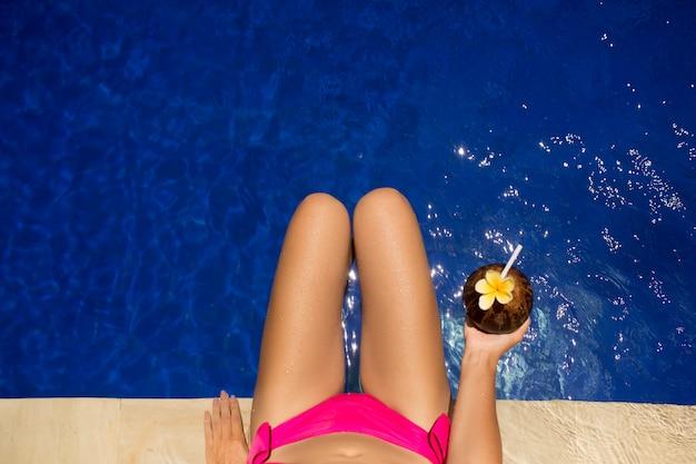 Dziewczyna trzyma napój kokosowy w niebieskim basenie, szczupłe nogi