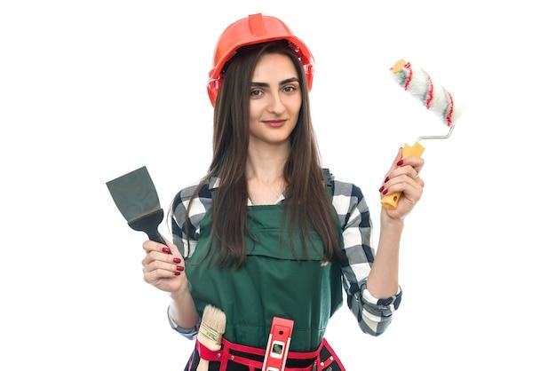 Dziewczyna trzyma narzędzia do malowania na białym tle