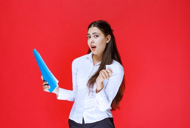 Dziewczyna trzyma niebieską teczkę i jej wizytówkę.