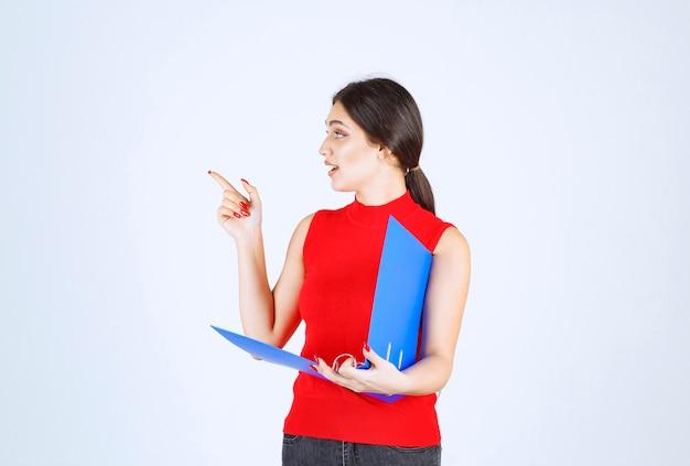 Dziewczyna trzyma niebieską teczkę i wskazuje na lewo.