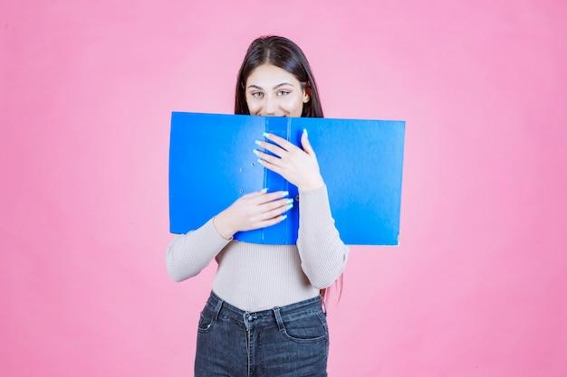 Dziewczyna trzyma niebieski folder projektu i chowa za nim twarz