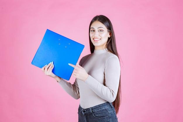 Dziewczyna trzyma niebieski folder projektu i wygląda na udaną i szczęśliwą