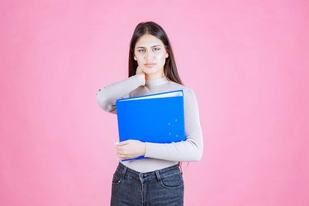 Dziewczyna trzyma niebieski folder raportu i wygląda na zmęczoną