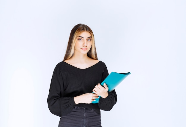 Dziewczyna trzyma niebieski folder raportu. zdjęcie wysokiej jakości