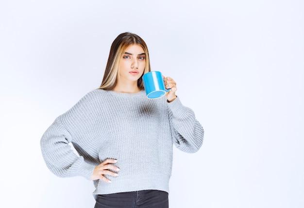 Dziewczyna trzyma niebieski kubek kawy i promuje go.