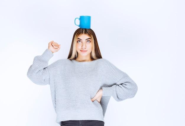 Dziewczyna trzyma niebieski kubek kawy na głowie.