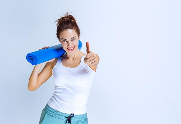 Dziewczyna trzyma niebieski matowy jogi i pokazuje kciuk w górę.