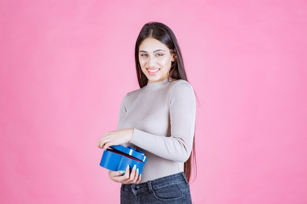 Dziewczyna trzyma niebieskie pudełko i uśmiechając się