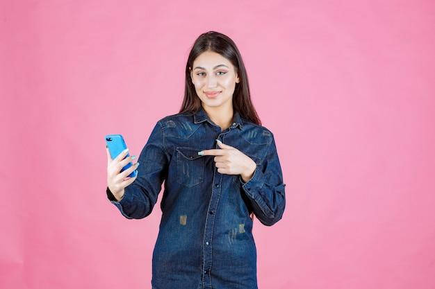 Dziewczyna trzyma nowy smartfon i wskazuje go