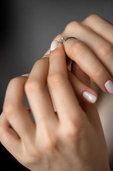 Dziewczyna trzyma obrączkę z brylantem na eleganckiej dłoni.