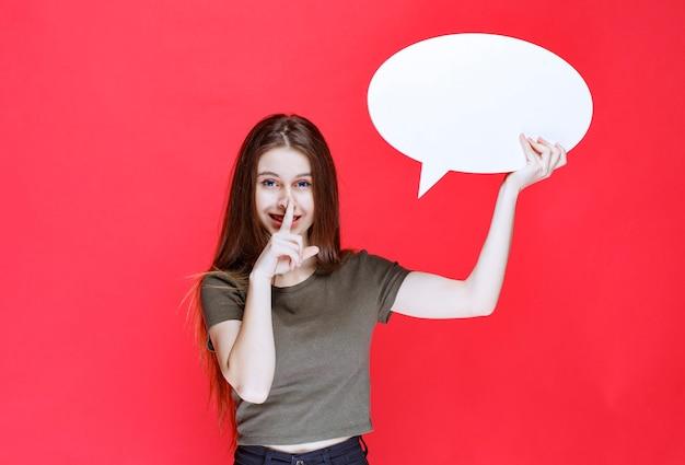 Dziewczyna trzyma owalną tablicę informacyjną i prosi o ciszę.
