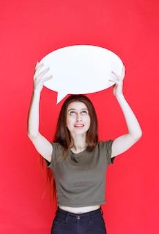 Dziewczyna trzyma owalną tablicę informacyjną nad głową.