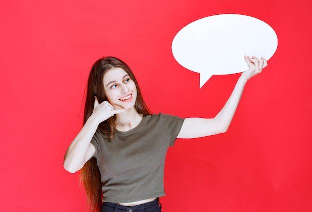 Dziewczyna trzyma owalną tablicę pomysłów i pokazuje jej uszy.