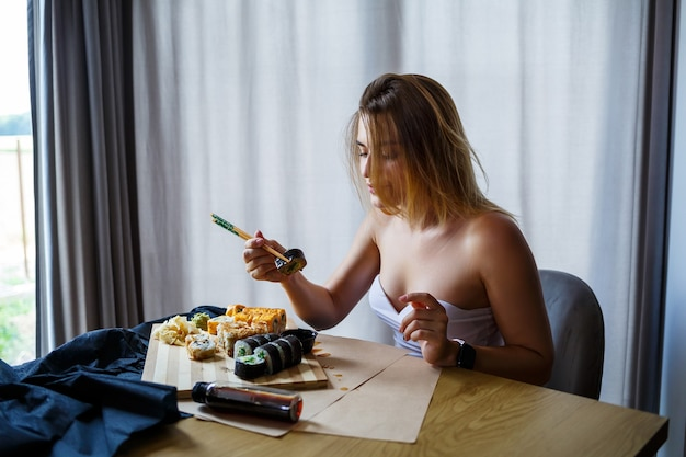 Dziewczyna trzyma pałeczki do sushi roll. młoda kobieta je pyszne sushi.