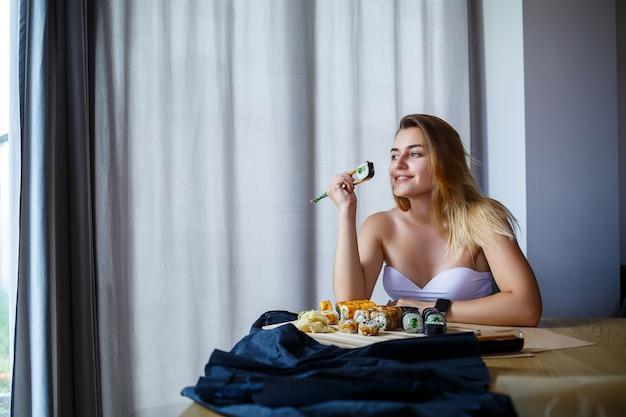 Dziewczyna trzyma pałeczki do sushi roll. młoda kobieta je pyszne świeże japońskie sushi.