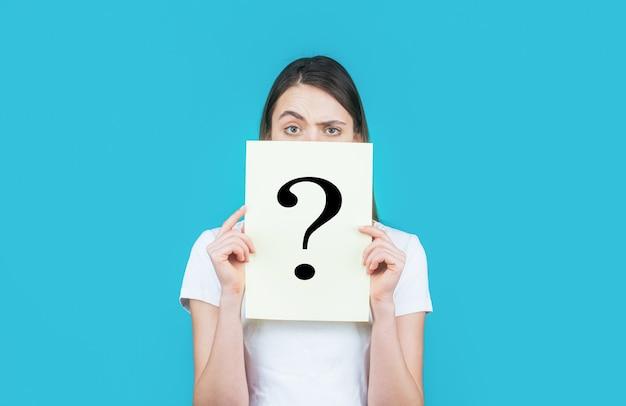 Dziewczyna trzyma papierowy znak zapytania. anonimowe, kobiece pytanie, incognita.