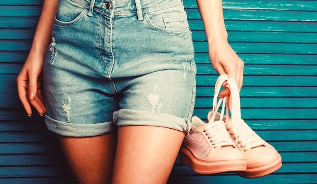 Dziewczyna trzyma parę butów. kobieta trzyma buty. kobieta trzyma parę różowych butów. dziewczyna z piękną talią w jeansowych szortach.