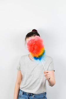 Dziewczyna trzyma pędzel do czyszczenia kurzu i zamyka twarz na szarej ścianie