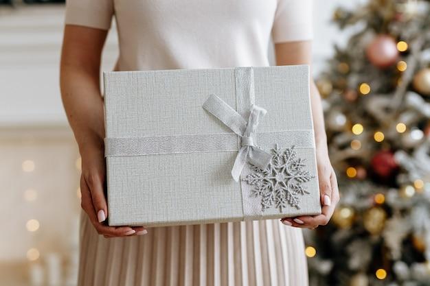 Dziewczyna trzyma piękne pudełko z prezentem na boże narodzenie