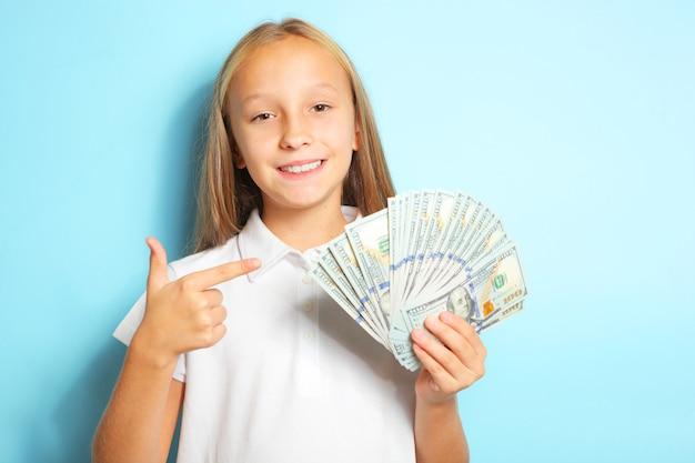 Dziewczyna trzyma pieniądze w rękach na niebieskim tle z bliska