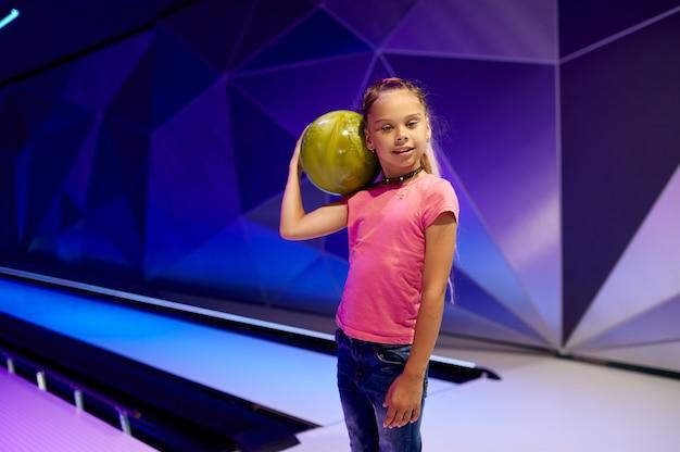 Dziewczyna trzyma piłkę na torze w kręgielni