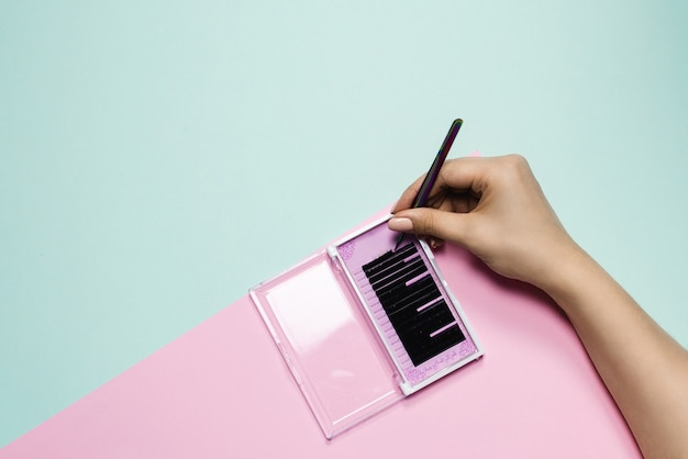 Dziewczyna trzyma pincetę nad różowym pudełkiem z czarnymi rzęsami na pastelowym tle. ręka kobiety bierze sztuczne rzęsy w celu przedłużenia. koncepcja przedłużania rzęs
