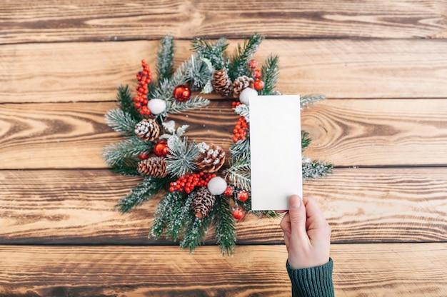 Dziewczyna trzyma pocztówkę na tle wieniec bożonarodzeniowy i drewniany stół. układ. miejsce do włożenia.