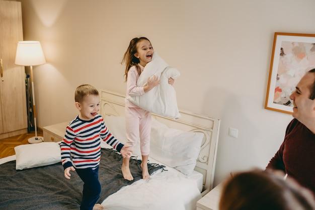 Dziewczyna trzyma poduszkę i bawi się z młodszym bratem