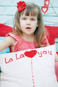 Dziewczyna trzyma poduszkę z sercem