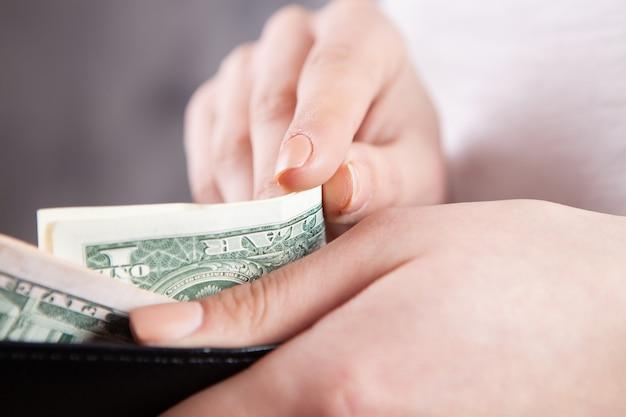 Dziewczyna trzyma portfel w dłoniach i bierze pieniądze