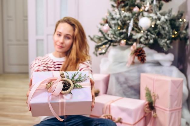 Dziewczyna trzyma prezent, choinkę, różowe pudełko z prezentem