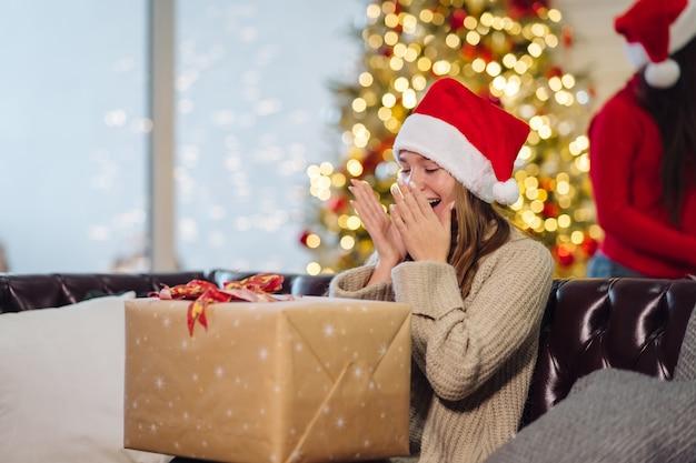 Dziewczyna trzyma prezent pod choinkę w boże narodzenie.
