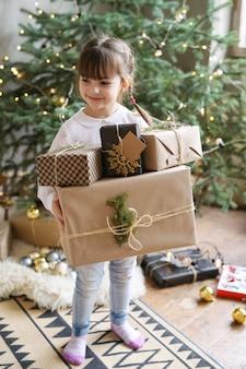 Dziewczyna trzyma prezent pod choinkę w boże narodzenie