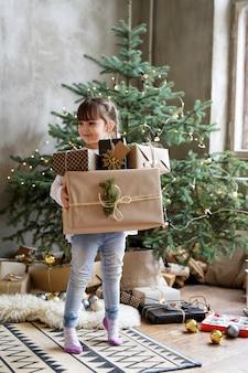 Dziewczyna trzyma pudełka na prezenty świąteczne