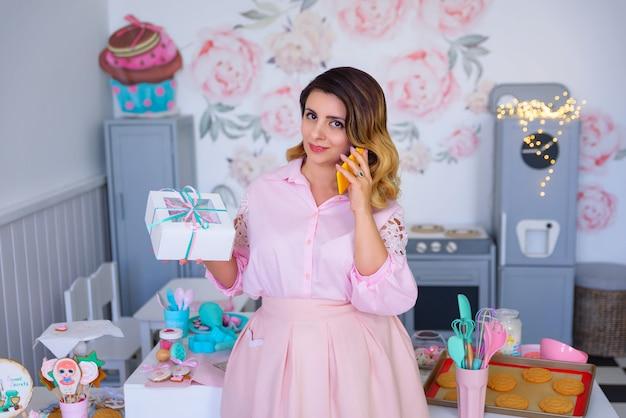 Dziewczyna trzyma pudełko i rozmawia przez telefon