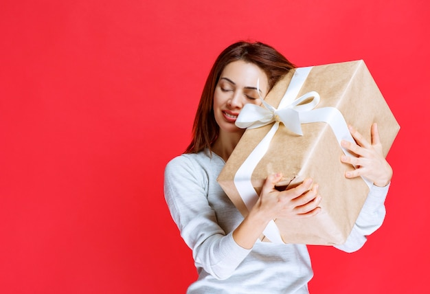 Dziewczyna trzyma pudełko i wygląda na zdziwioną i szczęśliwą.