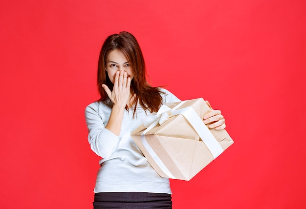 Dziewczyna trzyma pudełko i wygląda pozytywnie i pozytywnie.