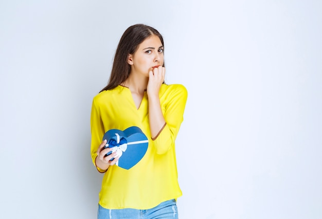 Dziewczyna trzyma pudełko na prezent w kształcie niebieskiego serca i myśli lub wahania.